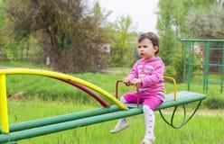 小逗人喜爱的女孩坐跷跷板在一个晴天 库存图片