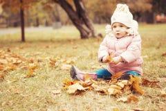 小逗人喜爱的女孩孩子获得乐趣在秋天温暖的衣裳& x28的公园; 库存照片