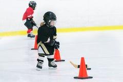 小逗人喜爱的女孩打在佩带在充分的曲棍球设备的冰的曲棍球 她做锻炼用棍子和顽童 库存图片