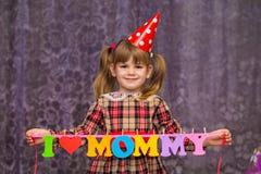 小逗人喜爱的女孩拿着有我爱五颜六色的纸字母表妈妈`的文本`的一本诗歌选 免版税图库摄影