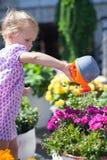小逗人喜爱的女孩浇灌的花用水 库存图片