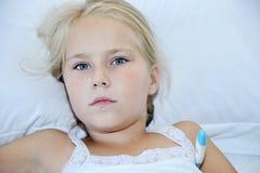 小逗人喜爱的女孩测量在白色背景的温度 免版税图库摄影