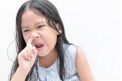 小逗人喜爱的女孩采摘她的鼻子,医疗保健 库存照片