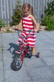 小逗人喜爱的女孩骑在礼服的一辆自行车  免版税库存照片