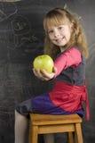 小逗人喜爱的女孩画象在黑板附近的 图库摄影