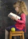 小逗人喜爱的女孩画象在黑板附近的 免版税库存图片