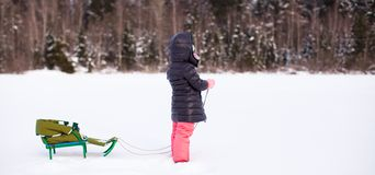 小逗人喜爱的女孩去sledding在一个温暖的冬日 免版税库存照片