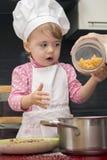 小逗人喜爱的孩子在厨房里倒在一个平底锅的面团 图库摄影