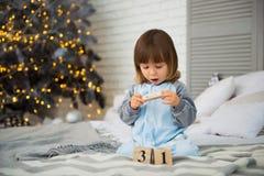 小逗人喜爱的小女孩是坐在圣诞树附近和看日历的2岁 12月31th 库存照片