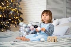 小逗人喜爱的小女孩是坐在圣诞树附近和看日历的2岁 12月31th 免版税库存照片