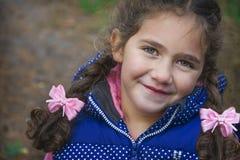 小逗人喜爱的愉快的女孩 使用两条卷曲猪尾 库存照片