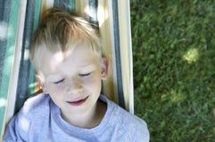 小逗人喜爱的摇摆和放松在吊床的儿童白肤金发的男孩 免版税库存图片