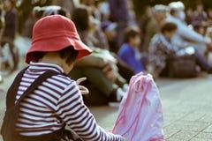 小逗人喜爱的日本女孩在学校在后面给坐与观众的地面穿衣 免版税库存图片
