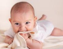 小逗人喜爱的滑稽的婴孩婴儿出牙用面孔表示手和手指在嘴 免版税图库摄影