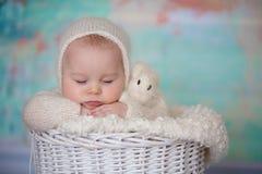 小逗人喜爱的男婴,打扮在手工制造被编织的白色女用连杉衬裤是 免版税库存图片