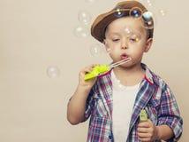 小逗人喜爱的男孩吹肥皂银行 库存照片