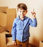 小逗人喜爱的男孩在空的屋子,对新房的remoove里 家庭单独 免版税库存图片