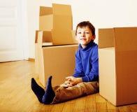 小逗人喜爱的男孩在空的屋子,对新房的remoove里 家庭单独emong箱子关闭孩子微笑 图库摄影