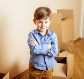 小逗人喜爱的男孩在空的屋子,对新房的remoove里 家庭单独emong箱子 免版税库存图片