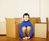 小逗人喜爱的男孩在空的屋子,移动里向新房 单独家在箱子中关闭微笑的孩子,生活方式真正的人民 库存照片