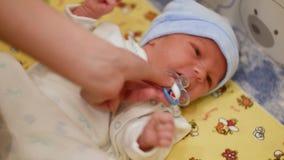 小逗人喜爱的男婴在有玩具的小儿床的,哭泣的男孩,母亲给孩子一名安慰者 影视素材