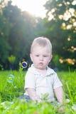 小逗人喜爱的白种人男孩画象单独坐草 免版税库存照片