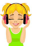 小逗人喜爱的白肤金发的女孩喜欢听到与耳机的音乐 库存图片