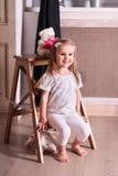小逗人喜爱的白肤金发的女孩坐小木梯子在屋子wi里 免版税库存照片