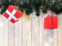 小逗人喜爱的红色欢乐礼物盒,圣诞节,在绿色圣诞节树分支背景的新年的装饰  免版税库存照片