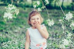 小逗人喜爱的被弄乱的女孩画象笑和获得乐趣户外在开花的树中在一个晴朗的夏日 免版税库存图片