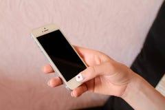 小配件智能手机在女孩的手上 免版税图库摄影
