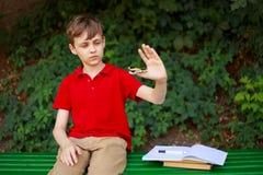 小配件瘾 使用与坐立不安锭床工人的男小学生  免版税库存照片