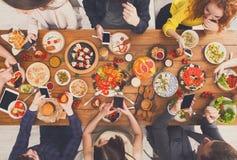 小配件设备瘾,愉快的人民吃与smarphones的晚餐 免版税图库摄影