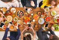 小配件设备瘾,与smarphones的朋友晚餐 免版税库存图片