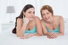 小野鸭在床上的无袖衫的愉快的女性朋友 免版税库存照片