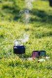 小钢水壶是在煤气喷燃器的煮沸在两钢杯子旁边 图库摄影