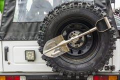 小铁锹和备用轮胎一辆越野车 库存图片