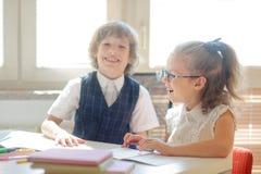 小门徒坐在学校书桌 库存照片