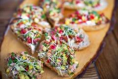 小雀跃和鱼肉 与被烘烤的三文鱼和蓬蒿特写镜头的Bruschetta在土气木桌上 从意大利烹调的盘 免版税图库摄影