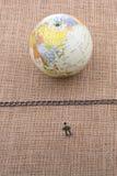 小雕象和地球与一个链子在中部 库存图片