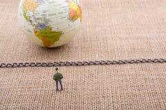 小雕象和地球与一个链子在中部 免版税库存照片