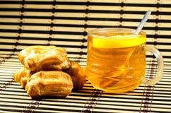 小饼和茶在一张竹席子 库存照片