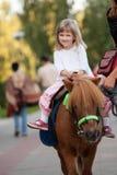 小马的愉快的微笑的小女孩 免版税库存照片