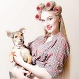 小鸡&小狗:有红色嘴唇&卷发的人的美丽的性感的白肤金发的画报女孩在她的举行一小逗人喜爱的狗愉快微笑的头发 免版税库存图片