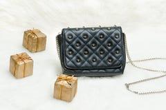 小黑袋子和礼物盒在白色毛皮 时兴的概念 库存照片