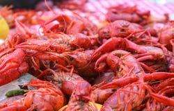 小龙虾煮沸-煮熟的在红色和白色堆的海鲜和菜检查了桌布 免版税图库摄影