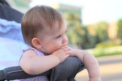 小,美丽,微笑,摇篮车外门的逗人喜爱的红头发人婴孩在握在他的嘴的一件无袖的衬衣手指 免版税库存照片