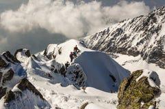 小组一个多雪的土坎的远足者 免版税图库摄影