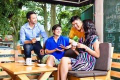 小组一家亚洲咖啡店的青年人 免版税库存图片