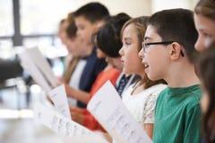 小组一起唱歌在唱诗班的小学生 库存照片